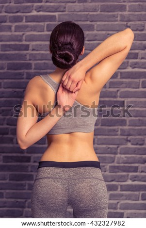 Back view of attractive young woman in sportswear stretching hands, standing against brick wall - stock photo