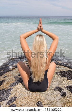 Back-view of beautiful Blonde in her swimwear practising yoga with the beach in front of her - stock photo