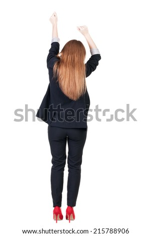 Back view of Beautiful business woman in suite looking at wall and Holds  hand up.  young brunette girl standing. Rear view people. Isolated over white background.  - stock photo
