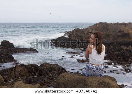 Back view of beautiful girl sitting on a rock by the ocean with copyspace - stock photo