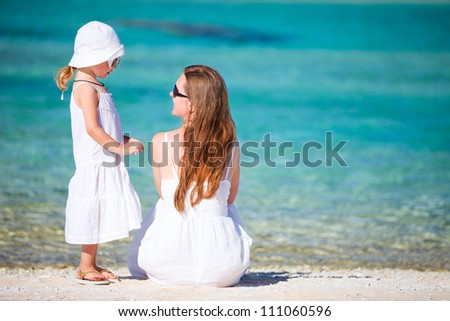Back view of beautiful mother and daughter on a tropical beach
