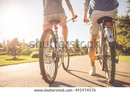 Back view of beautiful stylish couple cycling in the park, cropped