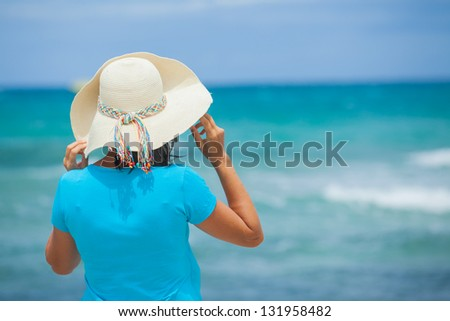 Back view of beautiful woman in the beach hat looking at the sea - stock photo