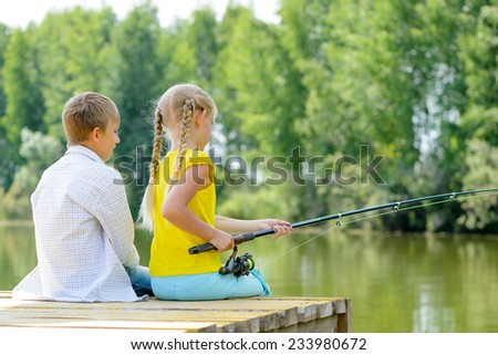 Back view of boy and girl sitting on wooden pier with rod - stock photo