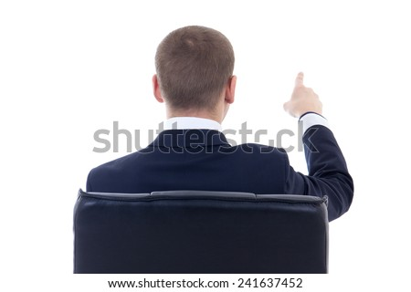 back view of business man sitting on office chair and pointing at something isolated on white background - stock photo