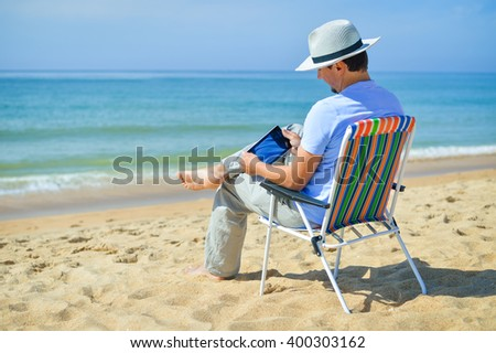 Back view of business man using smart phone or tablet computer on tropical beach blue sky background. Mockup top view  - stock photo