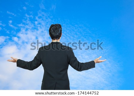 back view of businessman behind and presenting with blue sky - stock photo