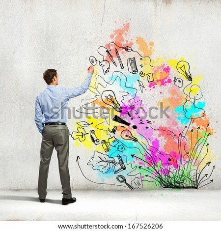 Back view of businessman drawing colorful business ideas on wall - stock photo