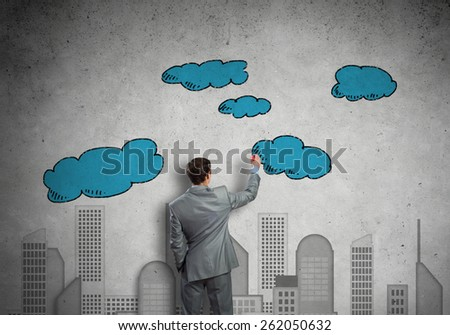 Back view of businessman drawing sketches of construction project on wall - stock photo