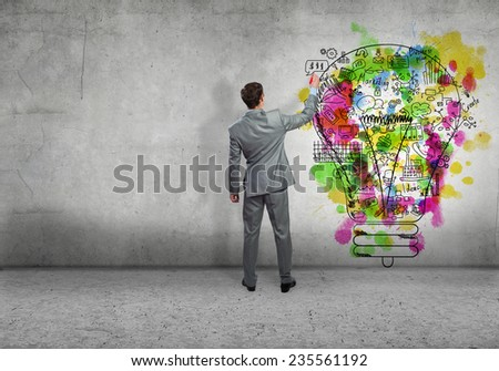Back view of businessman drawing sketches on wall - stock photo