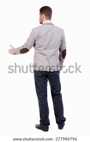 back view of businessman in jacket reaches out to shake hands. Rear view people collection. backside view of person.  A guy in a jacket with patches out his hand welcoming someone - stock photo