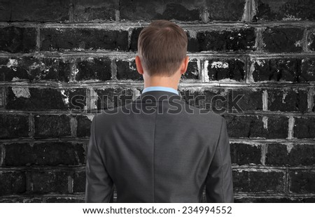 Back view of Businessman looking at brick wall - stock photo
