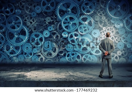 Back view of businessman looking at mechanism of cogwheels - stock photo