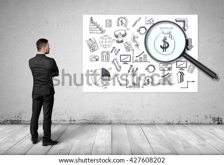 Back view of businessman looking at the bag of money through the magnifier. Economic and statistical graphs. Increase in profits. Making money. Prosperous business. Srategic calculation and research - stock photo