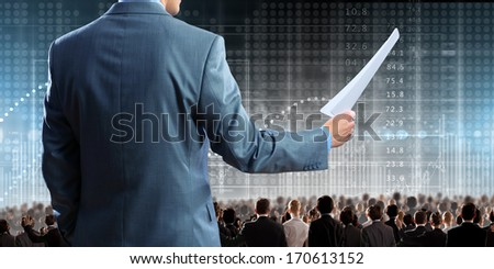 Back view of businessman speaker standing on podium in lights - stock photo