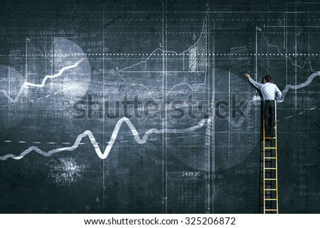 Back view of businessman standing on ladder and drawing sketch on wall - stock photo