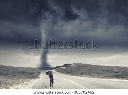 Back view of businessman with umbrella and suitcase facing tornado - stock photo
