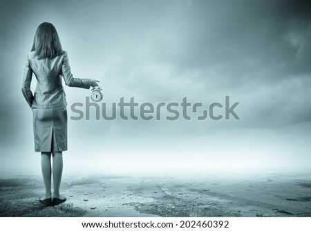 Back view of businesswoman holding alarm clock against cloudy background - stock photo