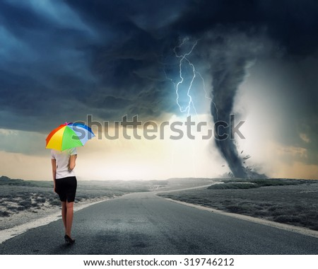 Back view of businesswoman in suit with colorful umbrella - stock photo