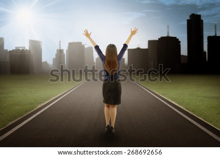 Back view of businesswoman showing happy body in positive mind on the road to reach a goal near the city view