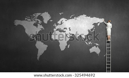 Back view of businesswoman standing on ladder and touching world map - stock photo