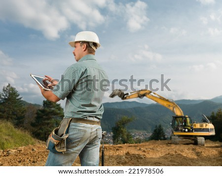 back view of caucasian engineer standing on construction site browsing on digital tablet - stock photo