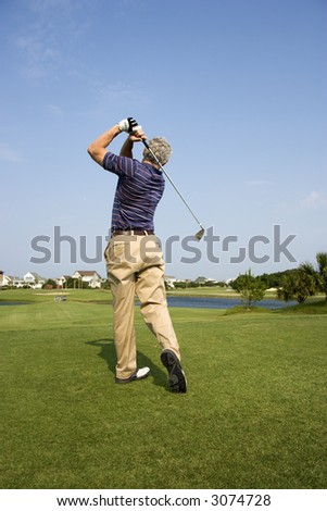 Back view of Caucasion mid-adult man swinging golf club. - stock photo