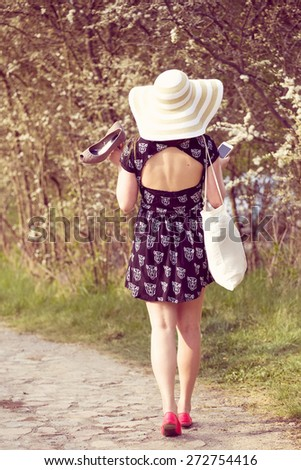 Back view of cheerful fashionable woman in stylish hat and frock posing outdoor. Happy brunette girl with shoes and summer bag in hand - stock photo
