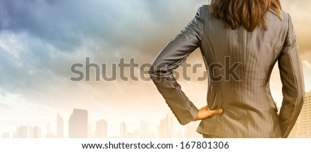 Back view of confident businesswoman with arm on waist - stock photo
