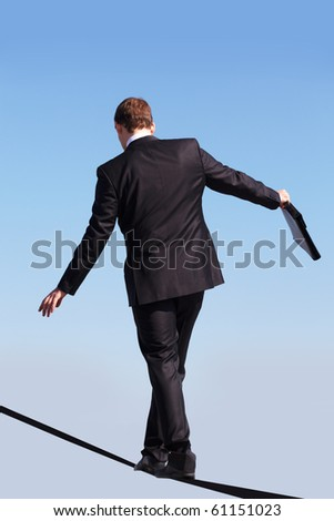 Back view of contemporary businessman walking down ribbon or rope with blue sky at background - stock photo