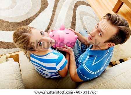 Back view of couple sitting on sofa with piggy bank - stock photo