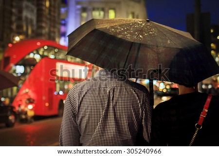 Back view of couple under the umbrella in the evening against the double-decker in London. Image with selective focus - stock photo