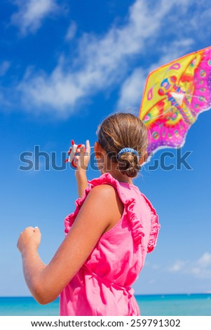 Back view of cute girl kite flying outdoor coast ocean - stock photo
