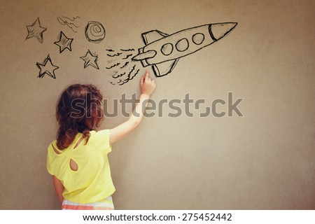 back view of cute kid (girl) imagine space rocket with set of infographics over textured wall background  - stock photo