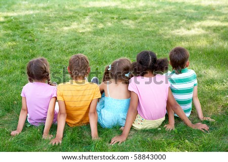 Back view of cute kids seated on green grass and relaxing - stock photo