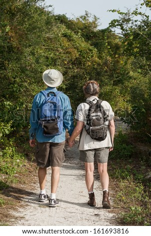 Back-view of cute mature couple hiking on nature trail while holding hands. - stock photo