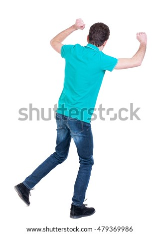 back view of dancing young man. Curly man in a turquoise sweater happily waving his hands.