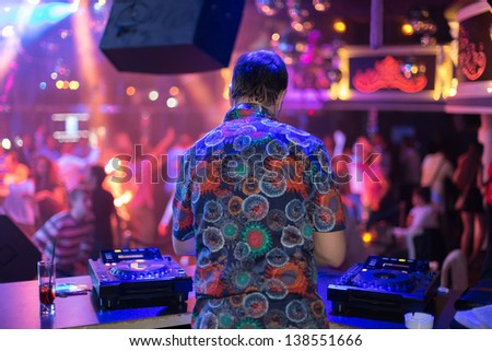 Back view of DJ turns the records at the club - stock photo