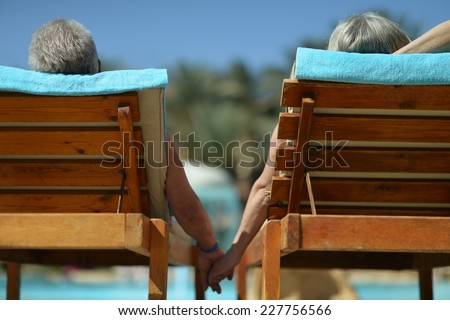 Back view of Elderly couple lying by pool at hotel resort - stock photo