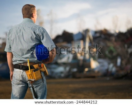 back view of engineer holding hardhat, standing in scrap metal recycling center. selective focus - stock photo