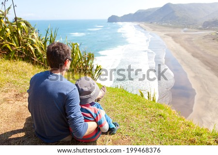 back view of family sitting at the top of lion rock at piha beach, new zealand - stock photo