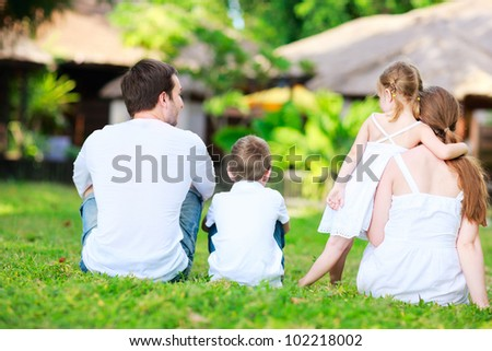Back view of family with two kids outdoors sitting on grass - stock photo