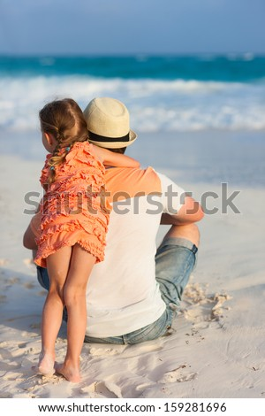 Back view of father and his little daughter at tropical beach - stock photo