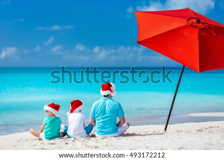 Back view of father and kids wearing red Santa hats enjoying beach vacation on Christmas