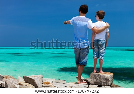 Back view of father and son on a tropical beach vacation - stock photo