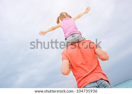 Back view of father carrying his little daughter on shoulders - stock photo