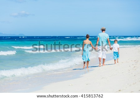 Back view of Father with his daughter and son walking on beautiful sunny beach