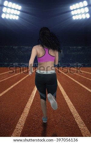 Back view of female runner wearing sportswear and doing exercise in the stadium at night