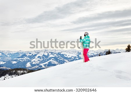 Back view of female snowboarder wearing colorful helmet, blue jacket, grey gloves and pink pants standing with snowboard in one hand against alpine mountain landscape - extreme sports concept - stock photo