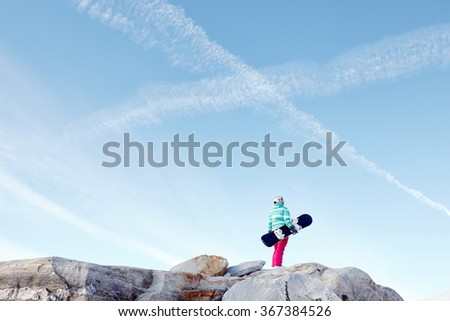 Back view of female snowboarder wearing colorful helmet, blue jacket, grey gloves and pink pants standing on rocks with snowboard in one hand against X sign on sky - winter sports concept - stock photo
